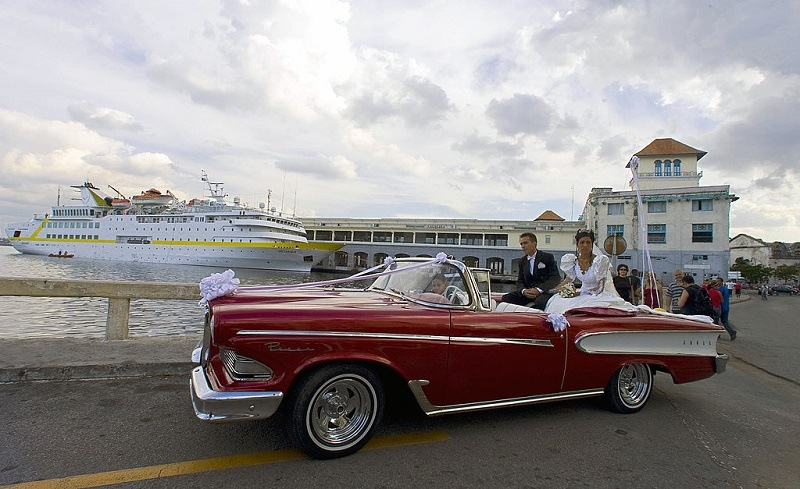 """A Cuban just married couple ride in a Ford Edsel 58 near the waterfront in Havana, on February 23, 2008. Cuba's National Assembly was to select Sunday a successor to Fidel Castro, likely his brother Raul Castro, extending the Americas' only communist one-party regime in defiance of US-led calls for political opening. Fidel Castro lashed out at Western appeals for democracy in the days leading up to the vote, which will trigger some readjustments in the political chessboard even as the transition bears the exiting leader's imprint. Saturday, Fidel Castro wrote in another editorial that he was eagerly awaiting the """"transcendental decision"""" of the National Assembly, and took a potshot at the US-based Organization of American States which does not allow Cuba to be a member due to its lack of democracy."""