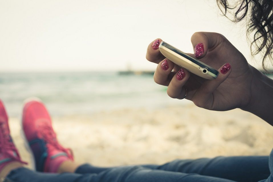 Girl on the beach and using a mobile phone to write Instagram captions