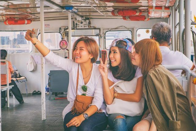 Group of happy smiling friends makes the photo while crossing the Chao Phraya River