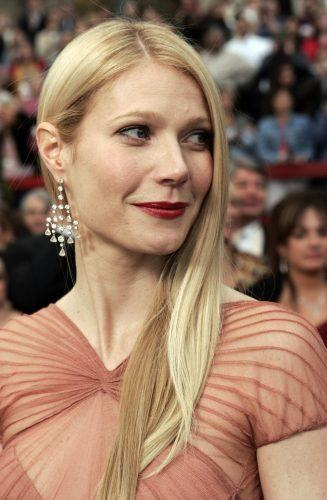 Gwyneth Paltrow wearing a red dress, smiling, and looking to her right.