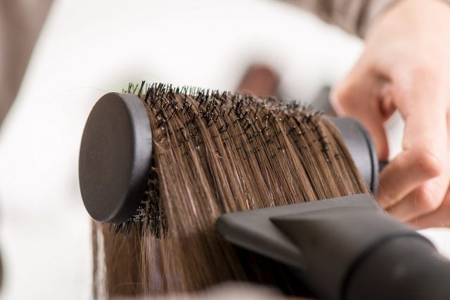 woman getting her hair brushed and dried