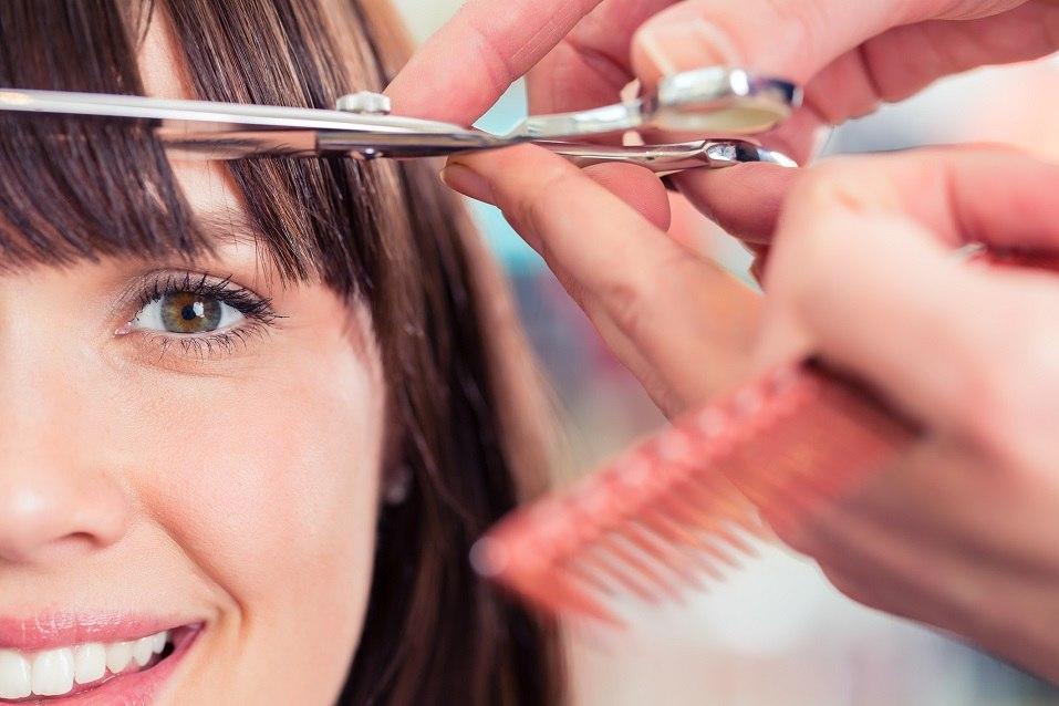 Hairdresser cutting woman bangs