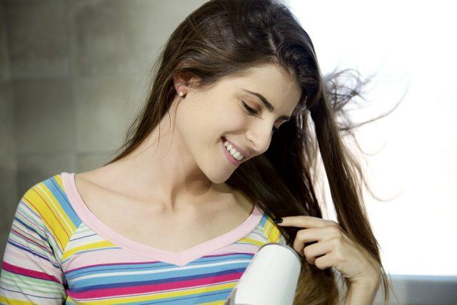 young lady blow drying long hair