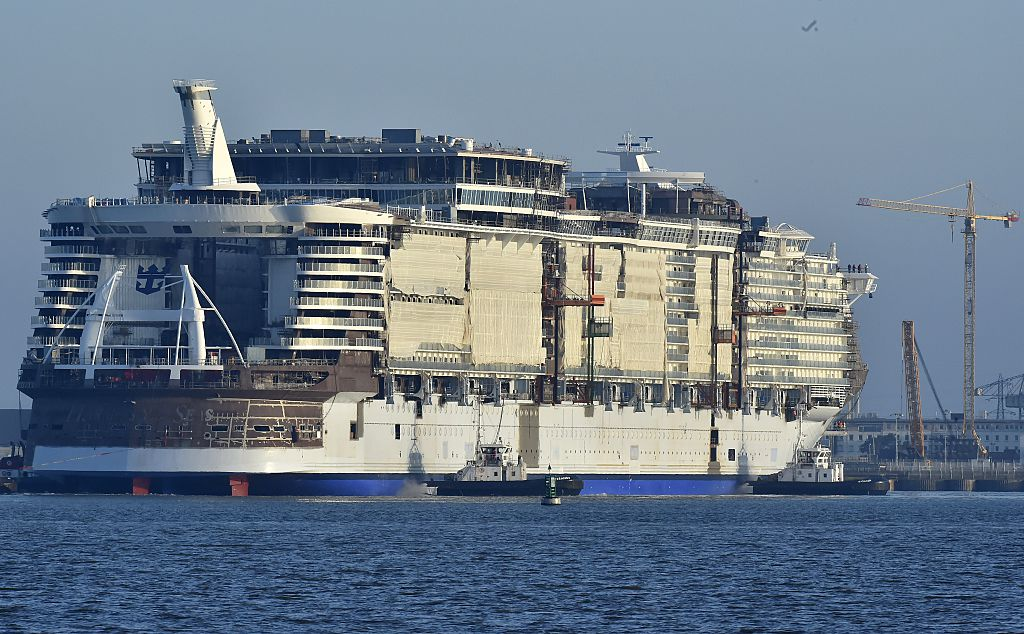 The cruise liner Harmony of the Seas is towed by tug boats into its new moorings at the STX Shipyards
