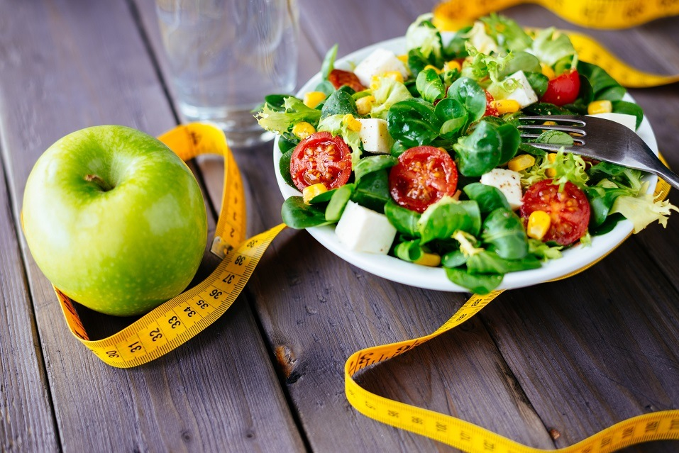 Fitness salad and apple fruit surrounded by measuring tape on rustic wooden table