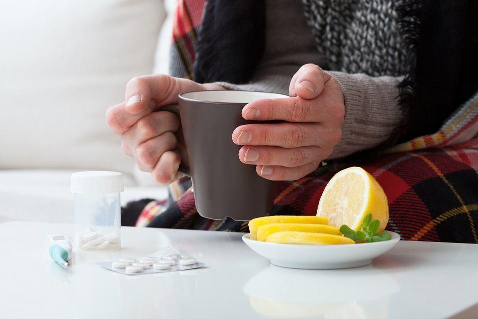 Ill man holding hot drink