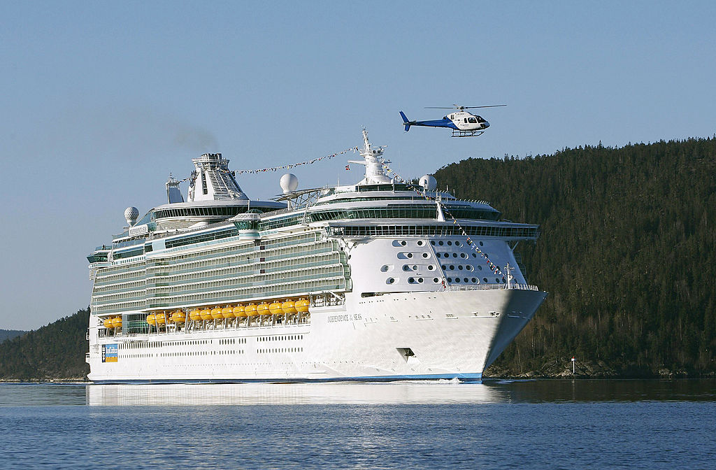 A helicopter flies over the Independence of the Seas cruise liner