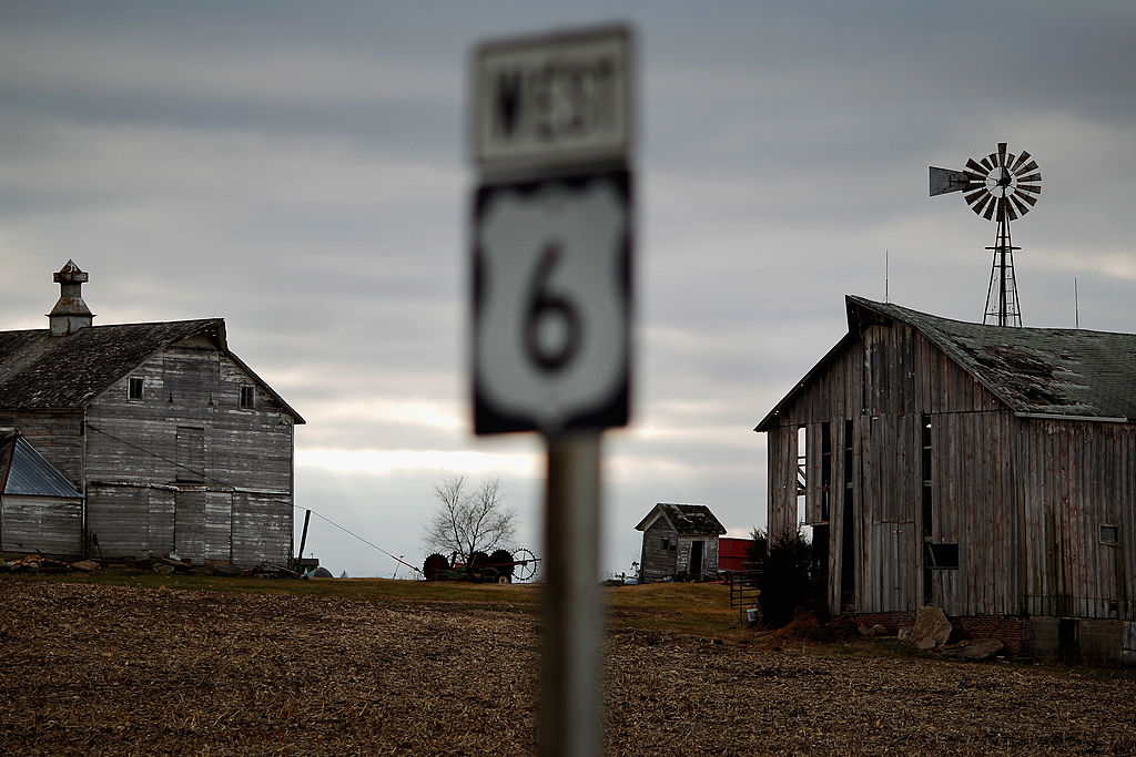 Weather-beaten farm buildings stand along an Iowa highway