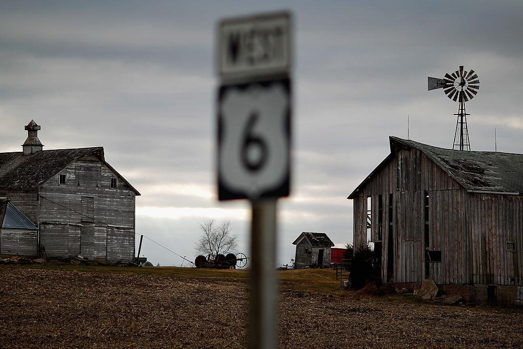 Weather-beaten farm buildings stand along Highway 6 in Iowa
