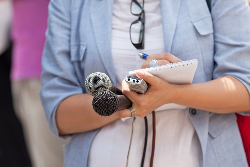 A reporter takes notes while holding several microphones and a recorder