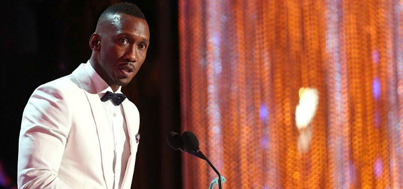 Mahershala Ali speaks into a microphone while on stage in a white tuxedo