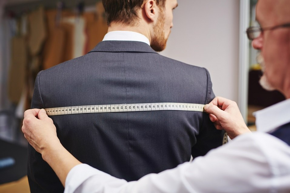 tailor measuring back of jacket worn by his client