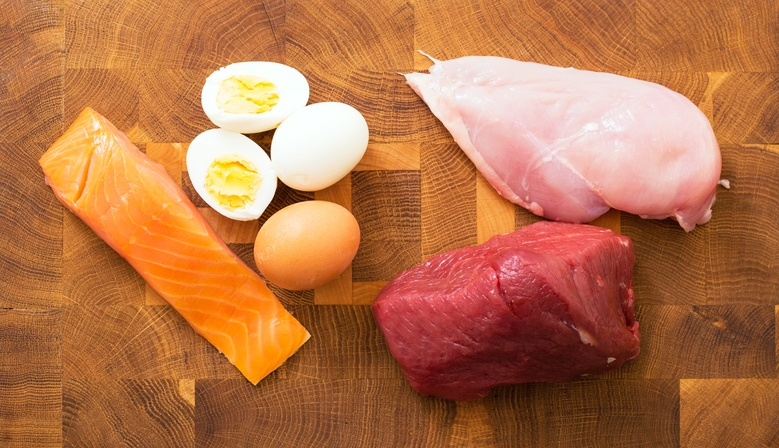 Meat, fish and eggs on wooden surface