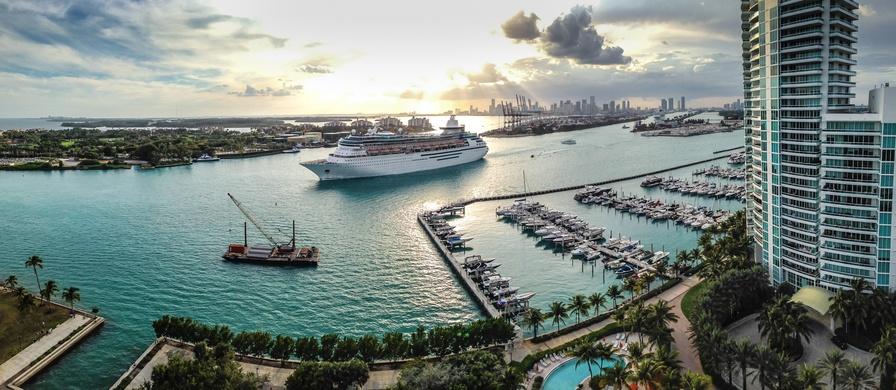 A panorama shot showing a cruise ship making its way down Miami Beach, Florida