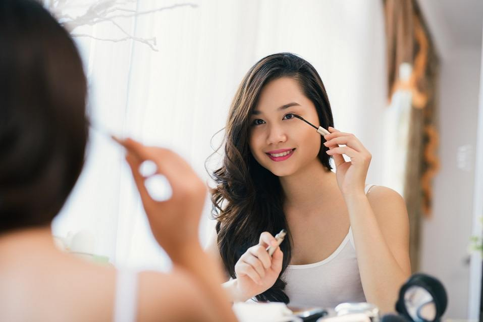 young girl applying mascara in front big mirror