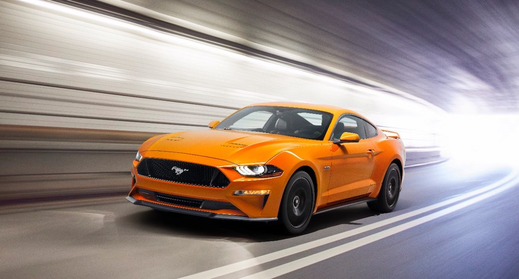 A bright orange 2018 Ford Mustang GT accelerates through a tunnel