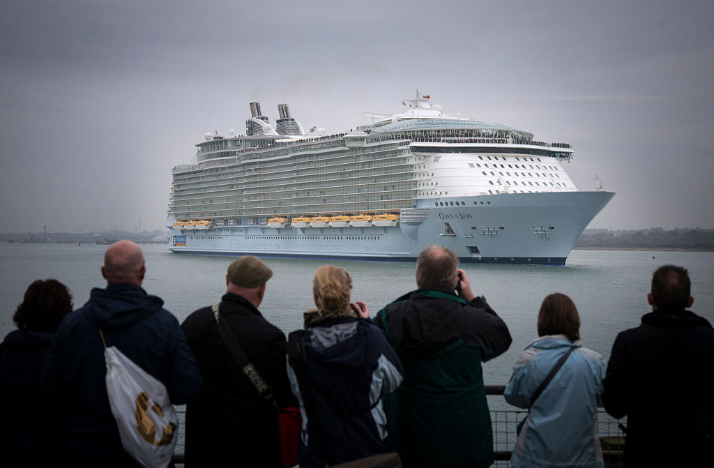 People taking pictures of Oasis of the Seas, one of the world's largest cruise ships, while it's anchored.