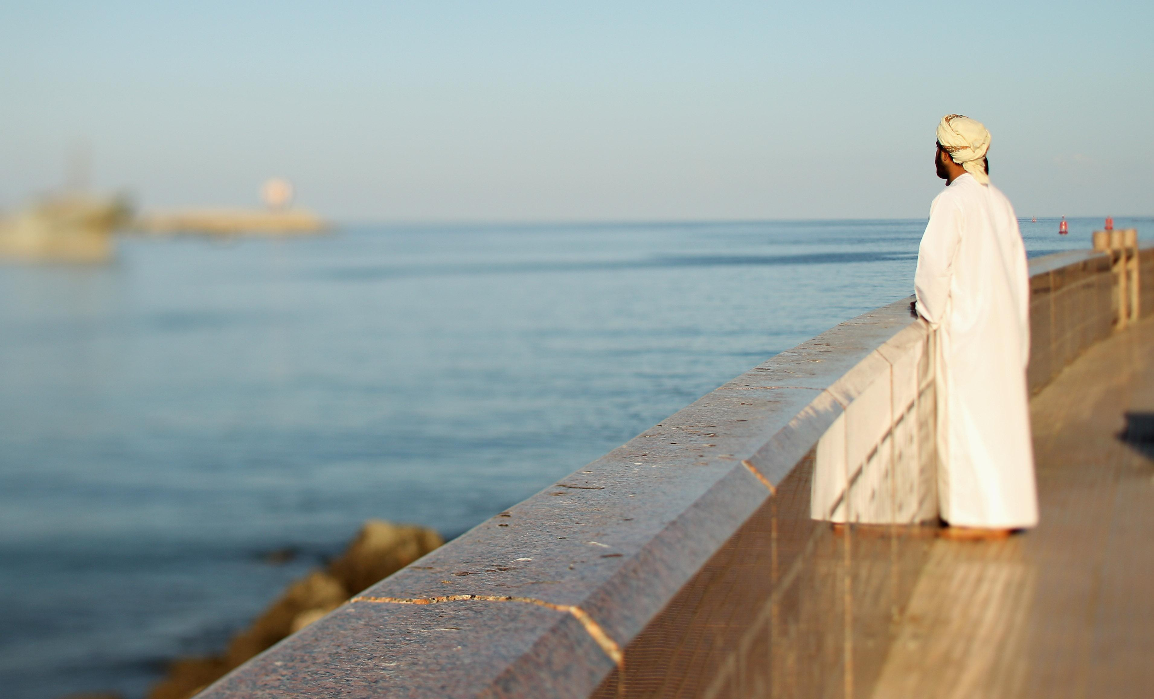 A local man looks out over Muscat harbor in Oman