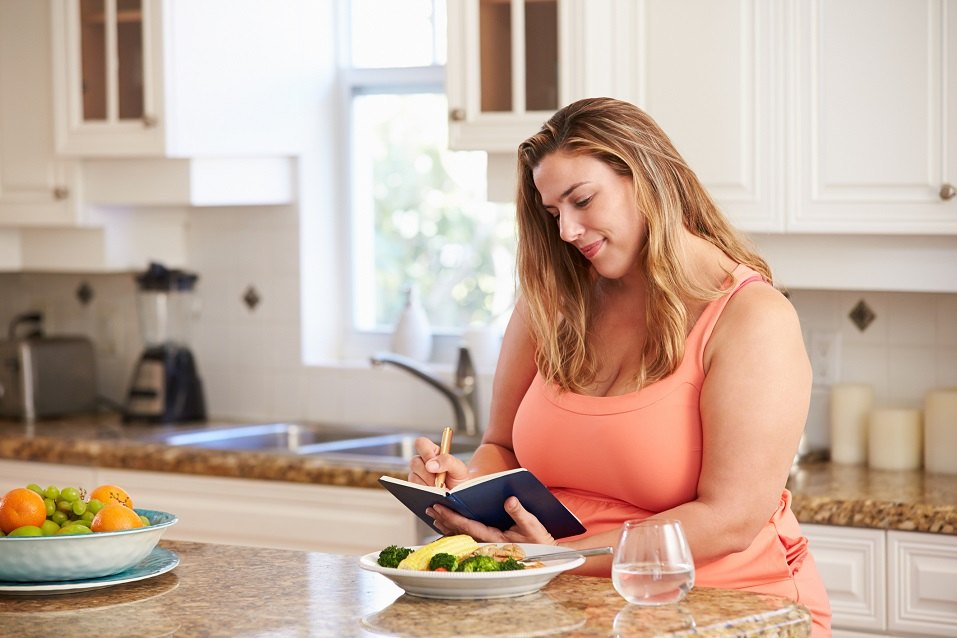 Woman writing down calorie consumption