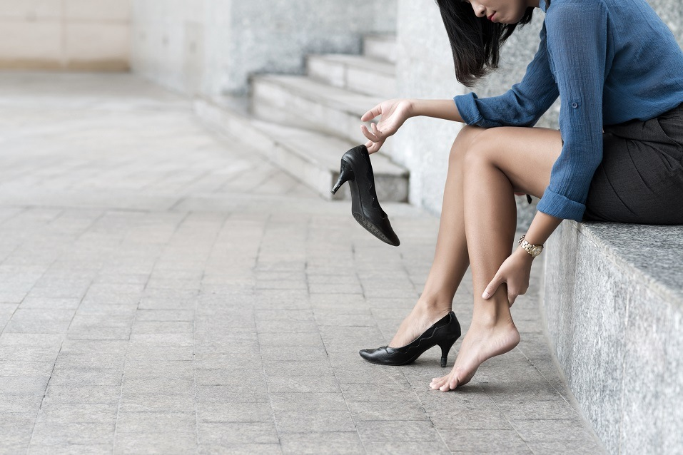Woman with shoe sitting outdoors and massaging ankle