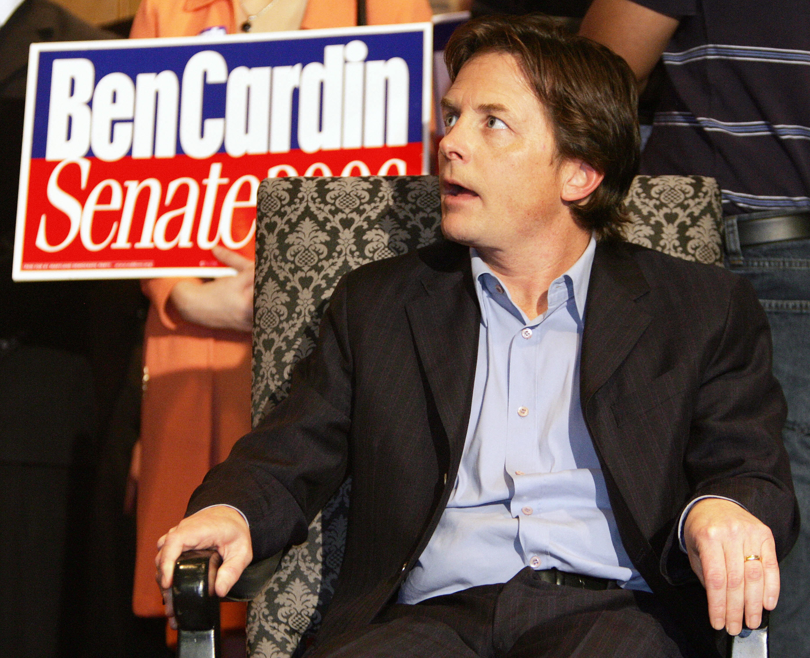 Michael J. Fox sitting in a chair at a political rally