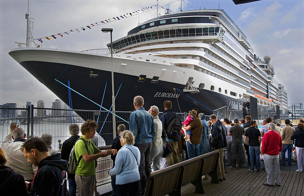 People watch the arrival of the MS Eurodam cruise ship