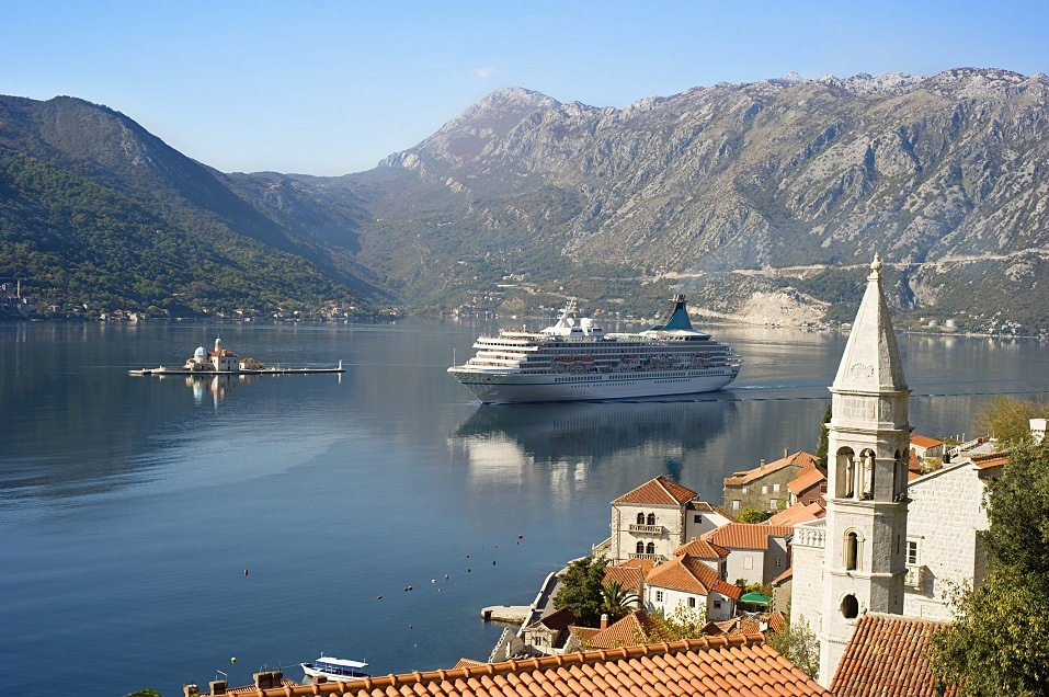 A cruise liner sails by Our Lady of the Rocks off the coast of Montenegro