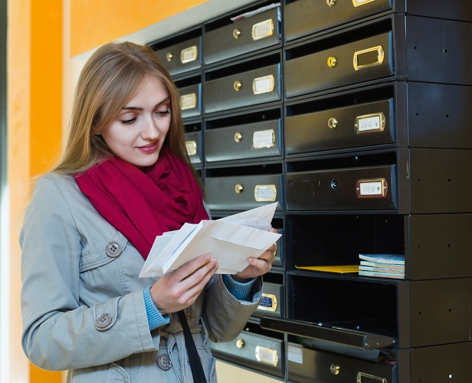 Girl in outwear receiving correspondence at hall entrance
