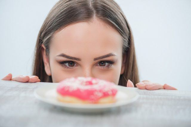 Beautiful girl is looking at unhealthy donut with appetite