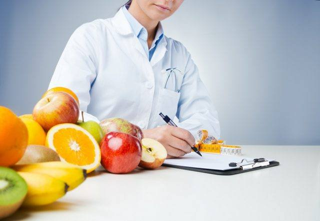 Nutritionist working at desk and writing medical records.