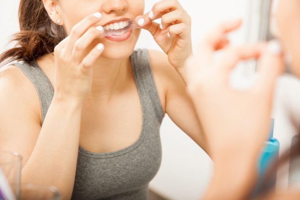 brunette applying a whitening strip on her teeth