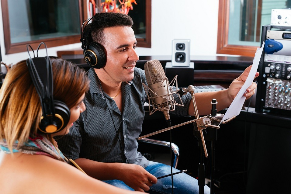 Male and female speaking into a microphone in a recording studio