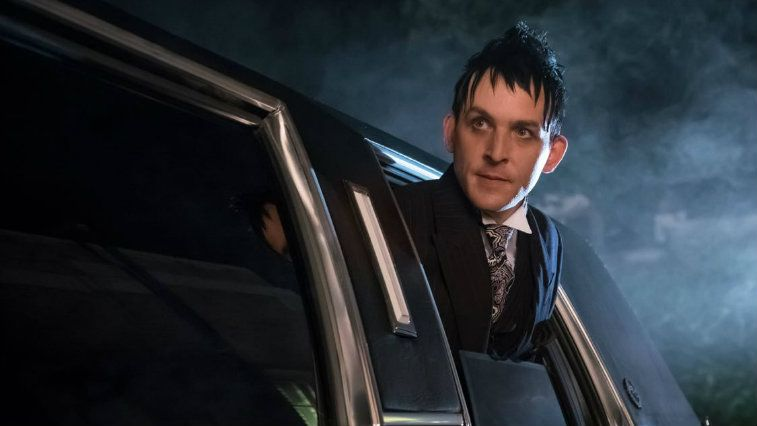 Robin Lord Taylor pokes his head out of a car window in Gotham