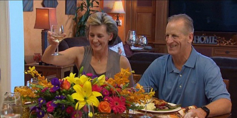 Jordan Rodgers' parents sit in front of dinner plates and hold up a glass of wine