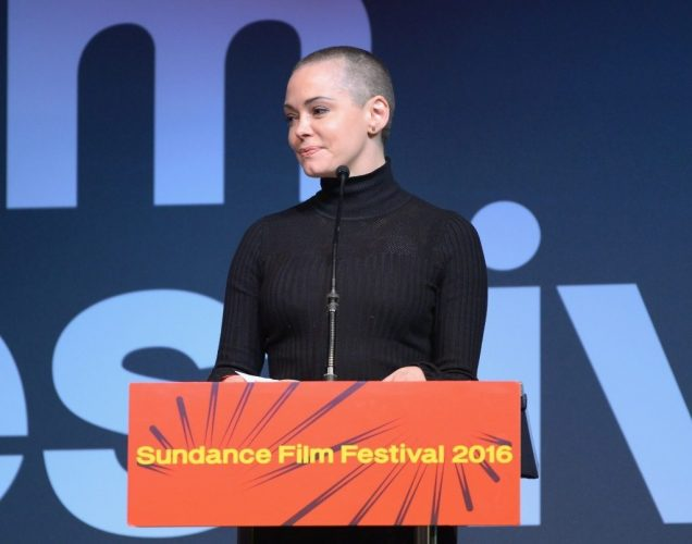 Rose McGowan standing in front of a podium and microphone.