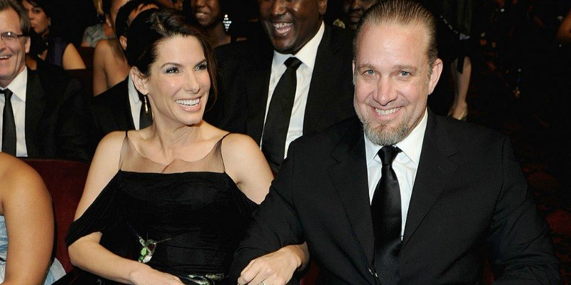 Sandra Bullock and Jesse James are sitting down in an audience smiling.