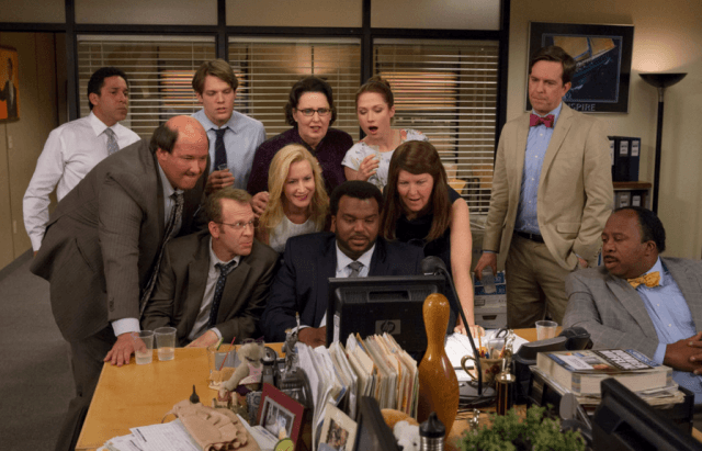 Employees on The Office gather around a computer.