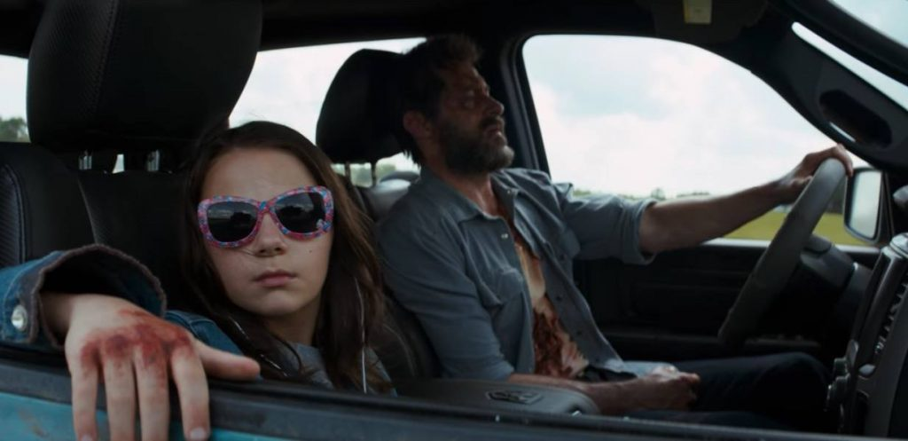 Logan and Laura driving in a car together, with Laura looking out the window to her right