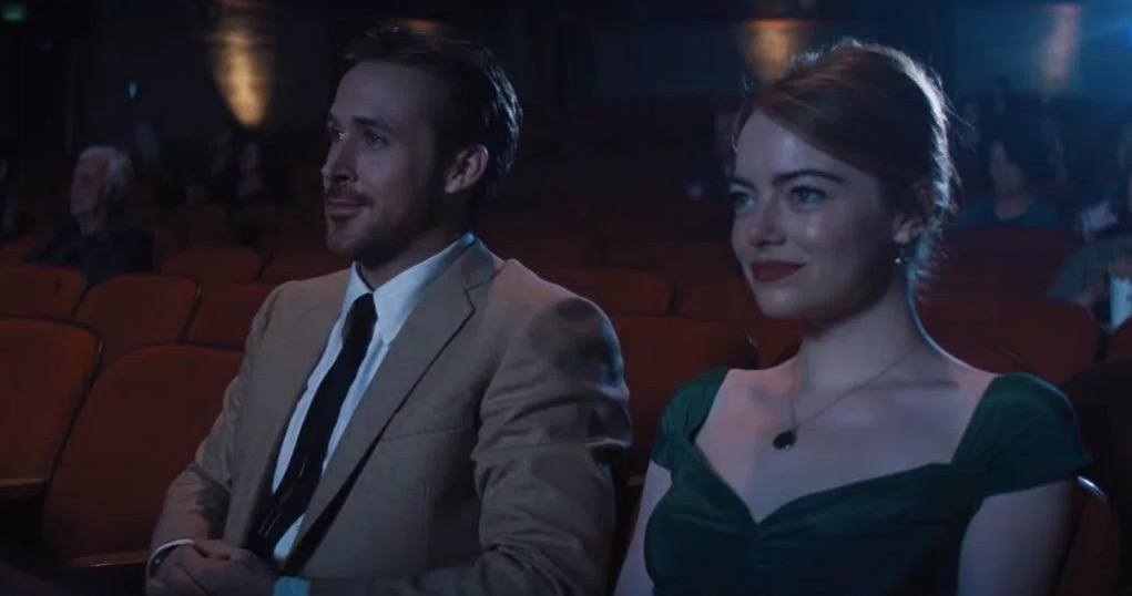 Ryan Gosling in a suit and Emma Stone in a green dress sitting in a darkened movie theater smiling
