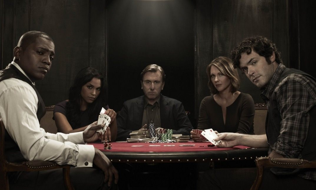 The cast of Lie to Me sits around a poker table looking at the camera
