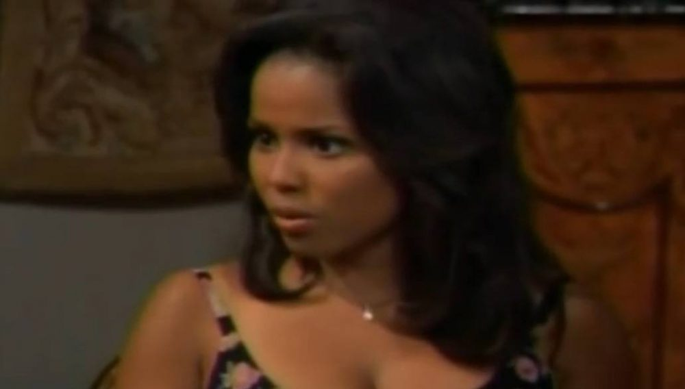 Michelle Thomas wearing a dress, looking to the left