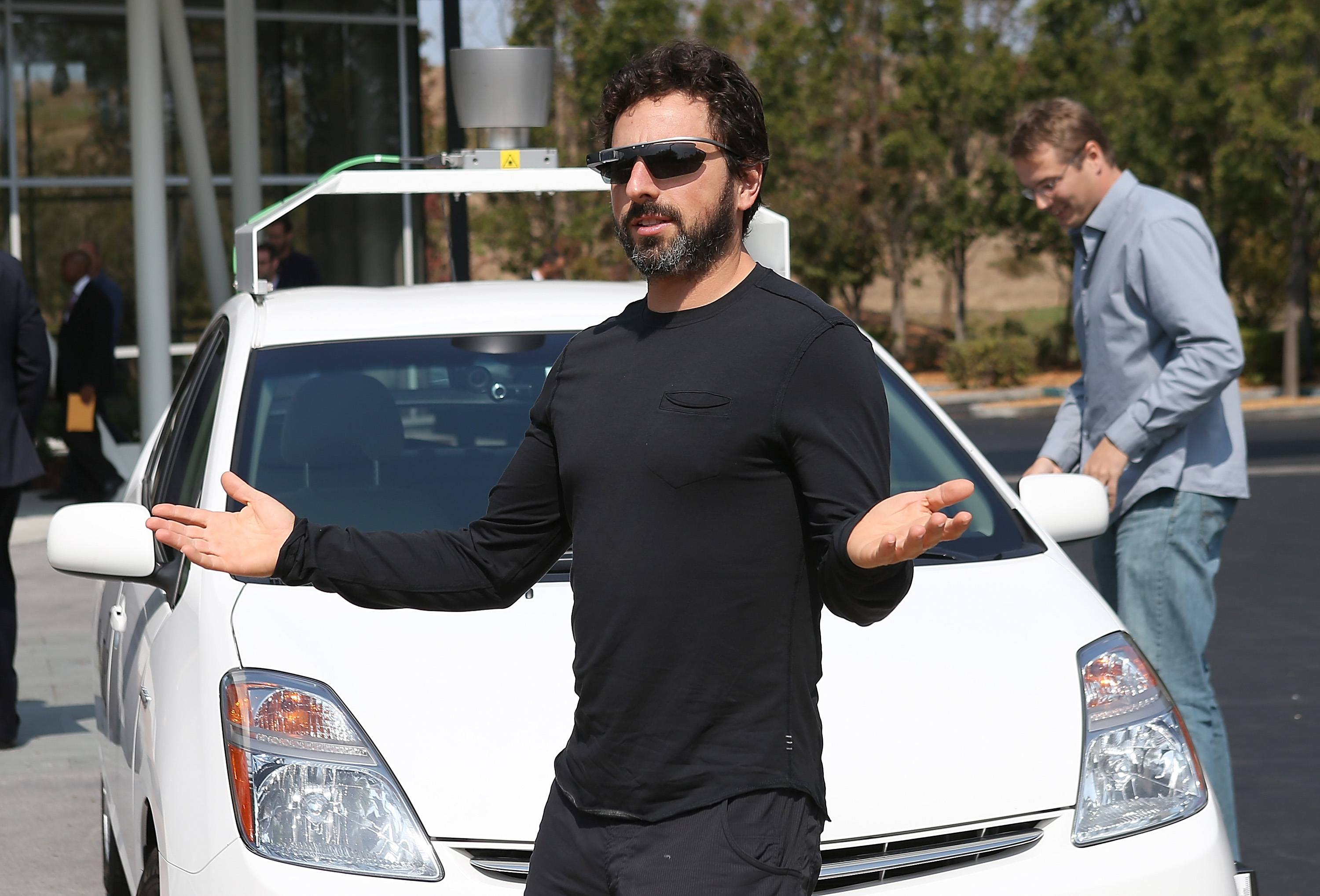 Google co-founder Sergey Brin stands in front of a self-driving car at the Google headquarters