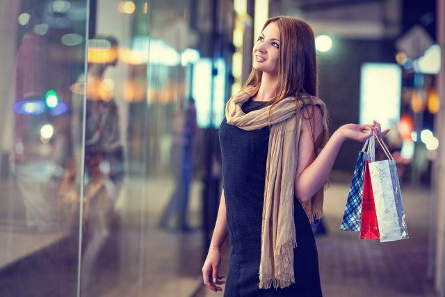 A woman carrying three shopping bags in her hand stops in front of a store's window and admires the display