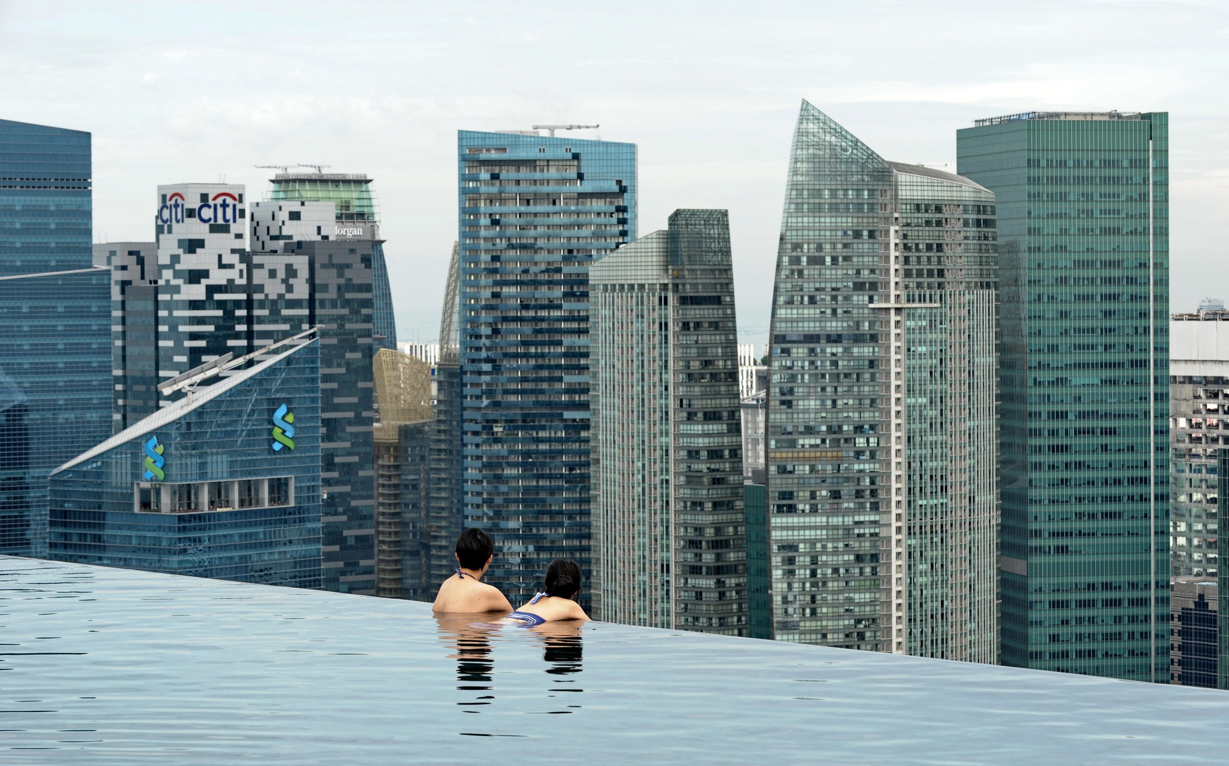 Visitors look at a view of the city skyline from the rooftop pool of the Marina Bay Sands resort hotel in Singapore
