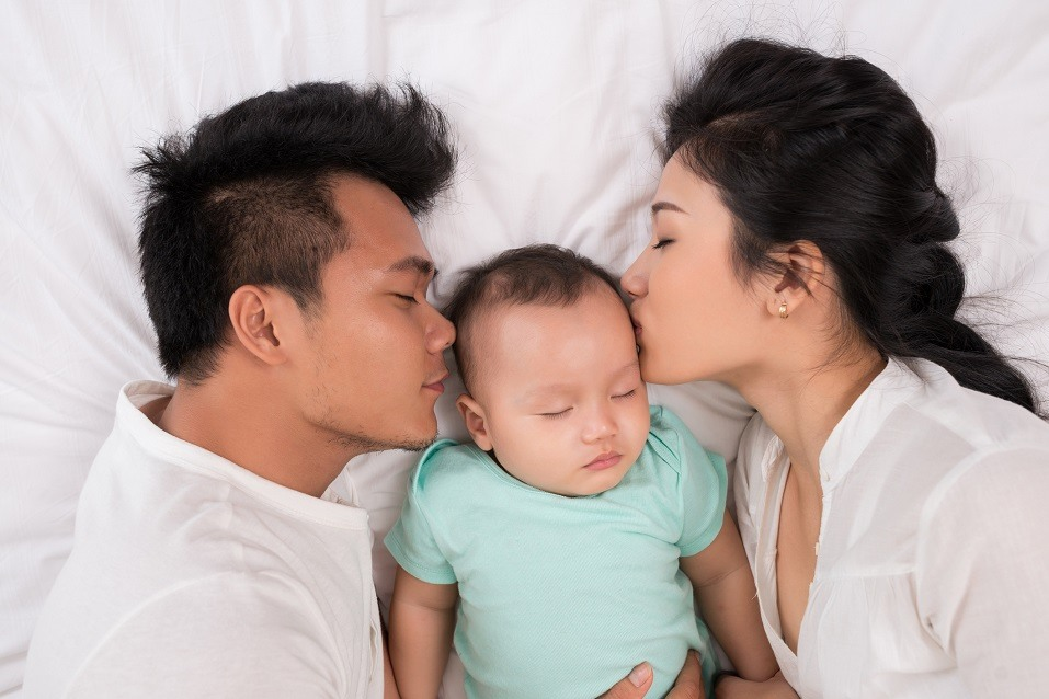 Asian family of three sleeping in bed