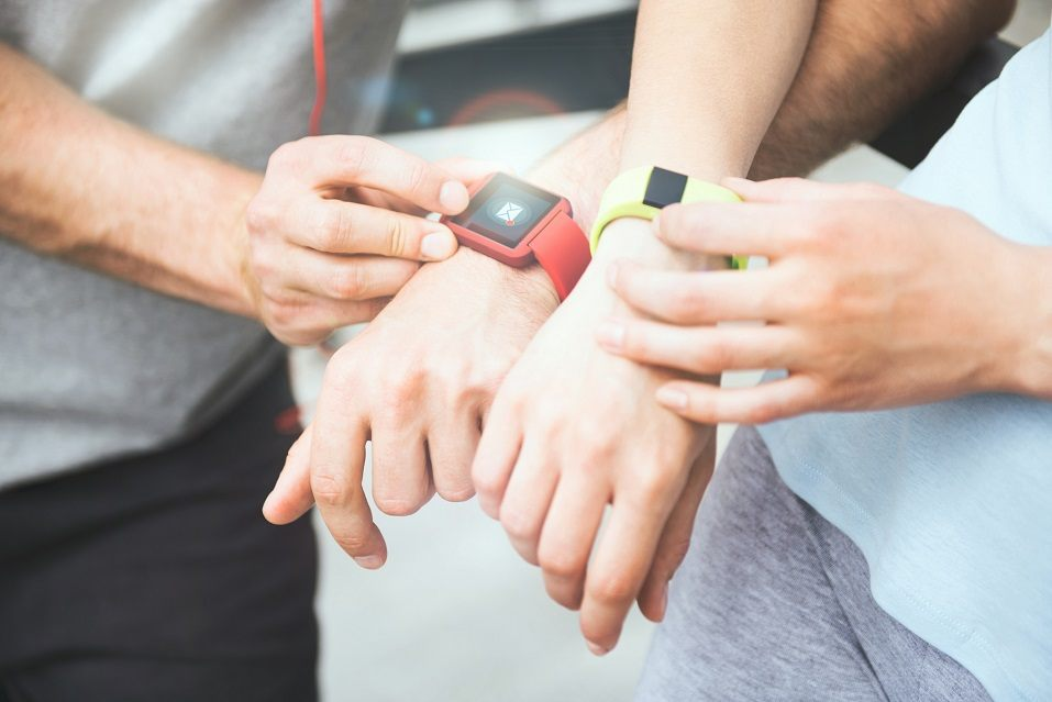 Active and sporty couple looking at their smartwatches