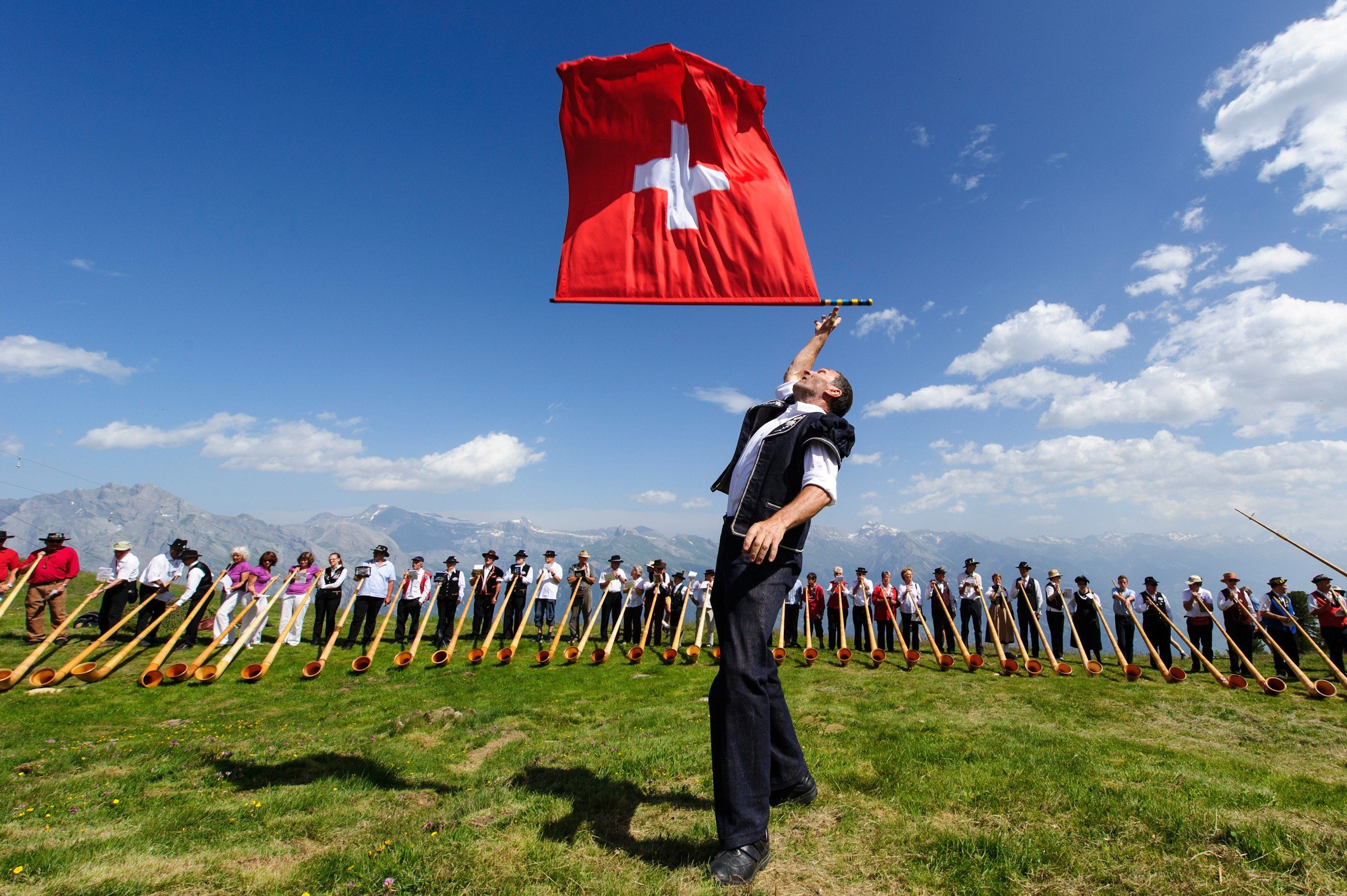 A man throws a Swiss flag as alphorn players perform
