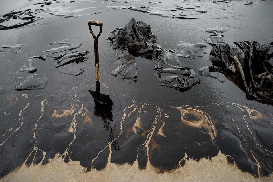 A shovel sits in oil-covered sand