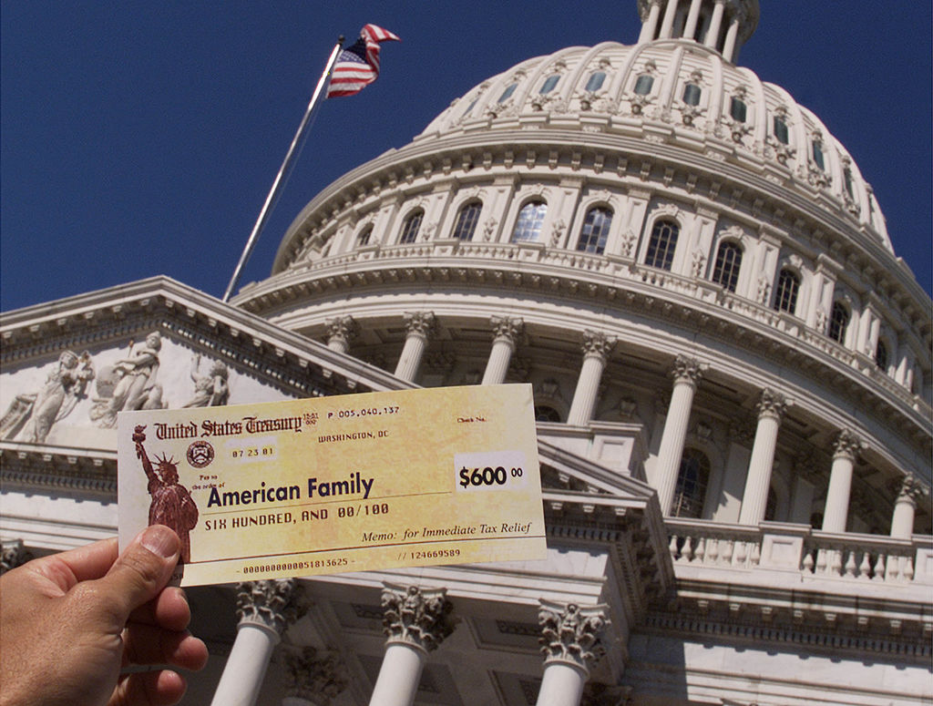 A man holds up a copy of a tax refund check