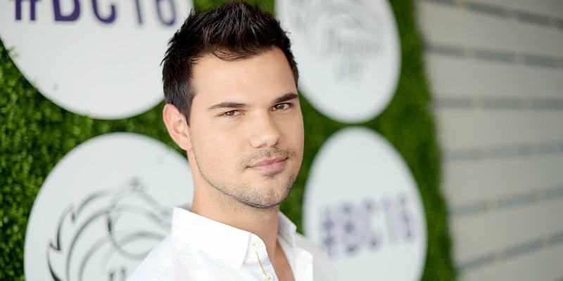 Taylor Lautner is smiling in a white shirt on the red carpet.